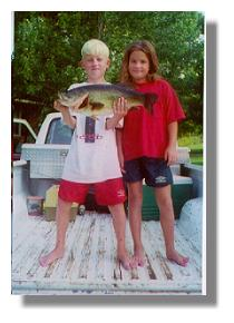 Hudson Wilson with his 7 1/2 lb bass caught from the pier on Lake Ely and his sister, Lauren (summer, 2001)